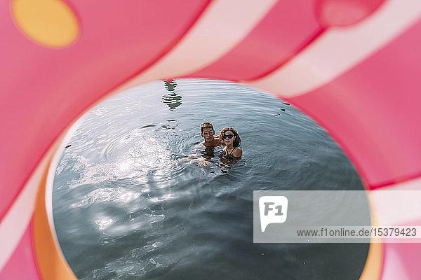 Junges Paar badet im Meer hinter einem aufblasbaren Schwimmer in Donutform