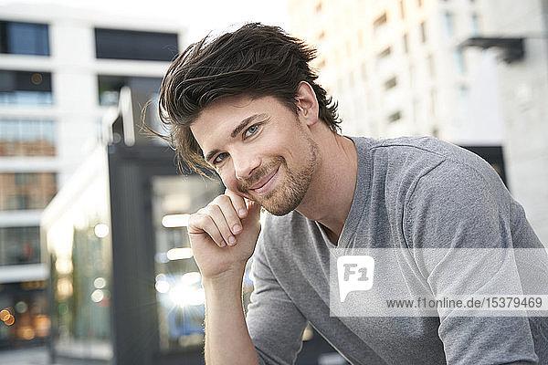 Porträt eines lächelnden Mannes mit grauem Hemd in der Stadt