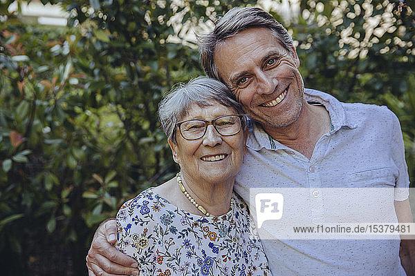Glückliche Mutter und erwachsener Sohn im Garten