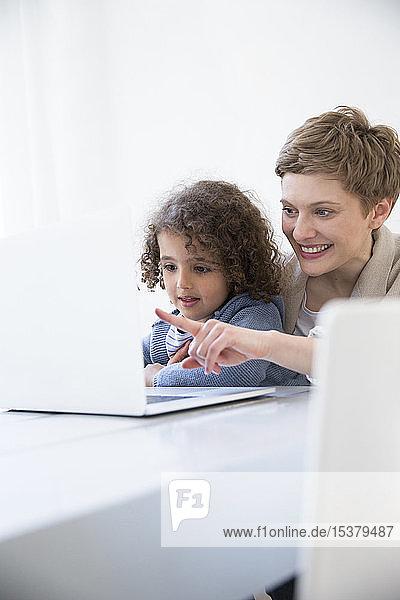 Lächelnde Mutter und Sohn benutzen Laptop zu Hause