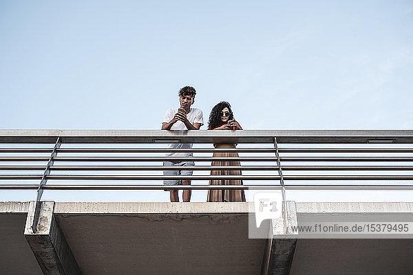 Junges Paar steht auf der Brücke und benutzt Smartphones Junges Paar steht auf der Brücke und benutzt Smartphones