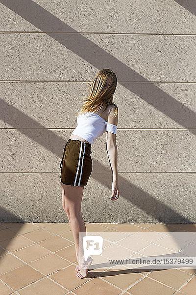 Junge  modische Frau auf den Zehenspitzen stehend  Gesicht unkenntlich gemacht