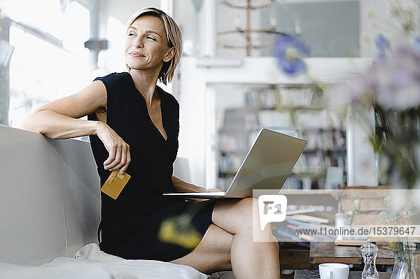 Businesswoman making online payment  sitting in coffee shop  using laptop and credit card