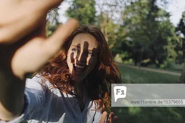 Glückliche rothaarige Frau trifft einen Freund in einem Park