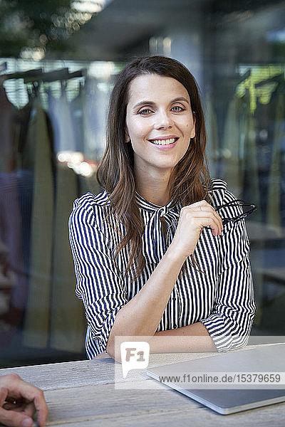 Porträt einer selbstbewussten Geschäftsfrau bei Tisch in der Stadt