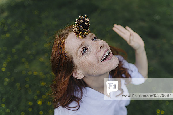 Redheaded woman balancing a pine cone on her forehead