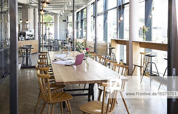 Laptop und Dokumente auf dem Tisch in einem modernen Café