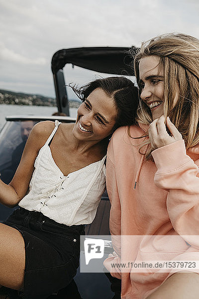Happy female friends on a boat trip on a lake