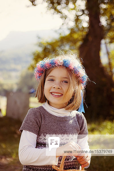 Portrait of a smiling young girl with hair wreath outdoors