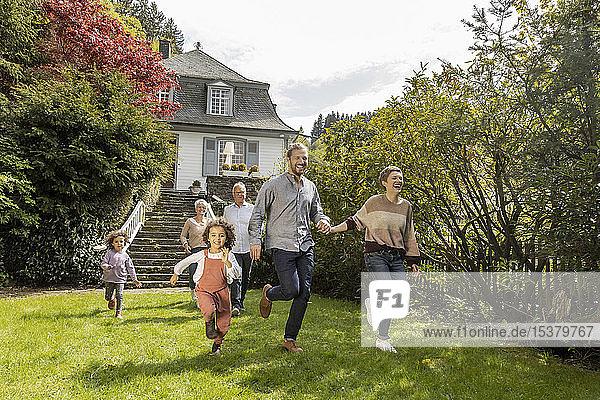Glückliche Großfamilie läuft im Garten ihres Hauses