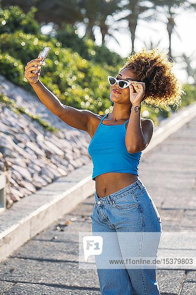 Porträt einer jungen Frau mit Sonnenbrille  die sich mit einem Smartphone selbstständig macht