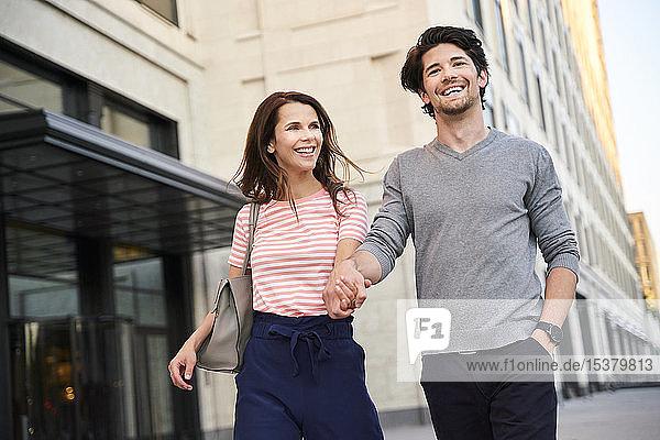 Glückliches Paar geht in der Stadt Hand in Hand