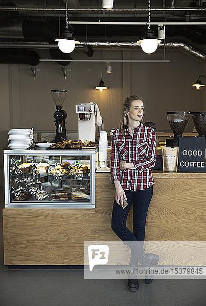 Frau,  die an der Theke eines Cafés steht und sich umsieht