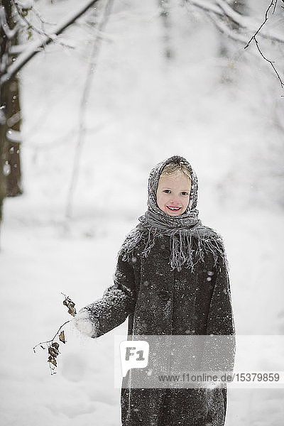 Portrait of little girl wearing headscarf and coat standing in winter forest holding twig with autumn leaves