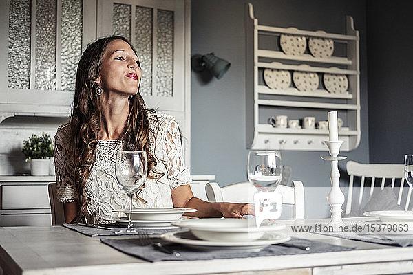 Grinsende junge Frau sitzt am gedeckten Tisch in einer Küche im Landhausstil