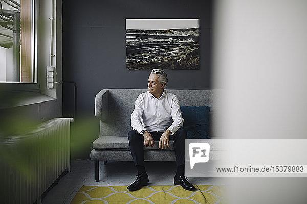 Leitender Geschäftsmann auf einer Couch sitzend