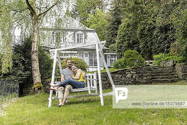 Entspanntes Paar im Garten seines Hauses