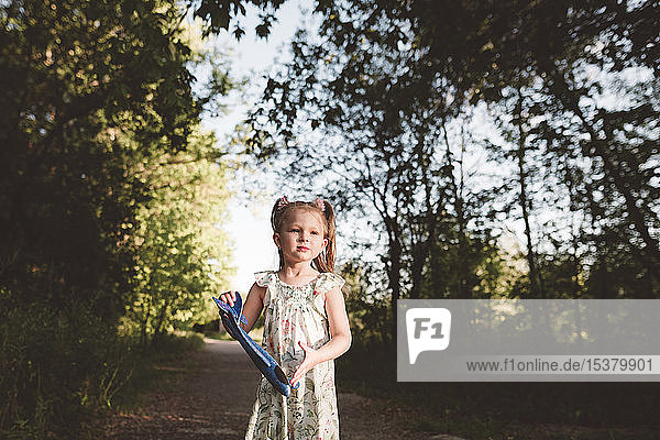 Lttle girl holding toy airplane in the forest