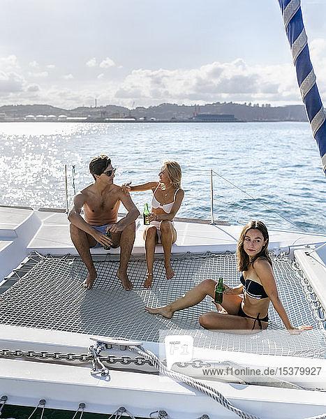 Drei junge Freunde genießen einen Sommertag auf einem Segelboot