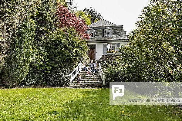 Großfamilie  die auf einer Treppe im Garten ihres Hauses sitzt