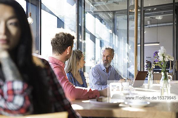 Gelegentliche Geschäftsleute,  die eine Besprechung in einem Café abhalten