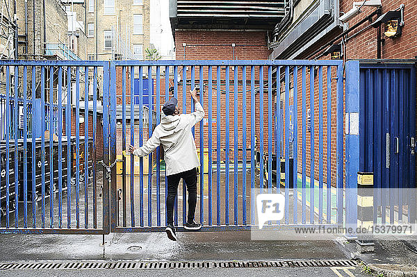 Back view of man climbing gate