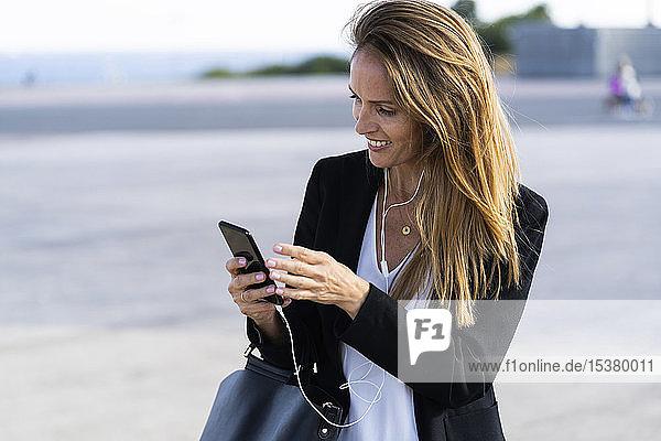 Lächelnde Geschäftsfrau mit Smartphone und Kopfhörern im Freien