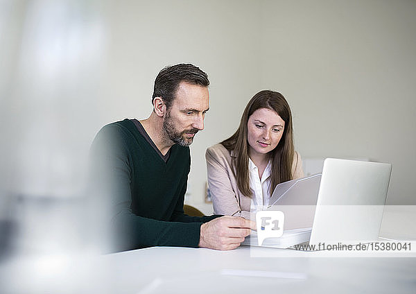 Businessman and employee with laptop and documents working at desk in office