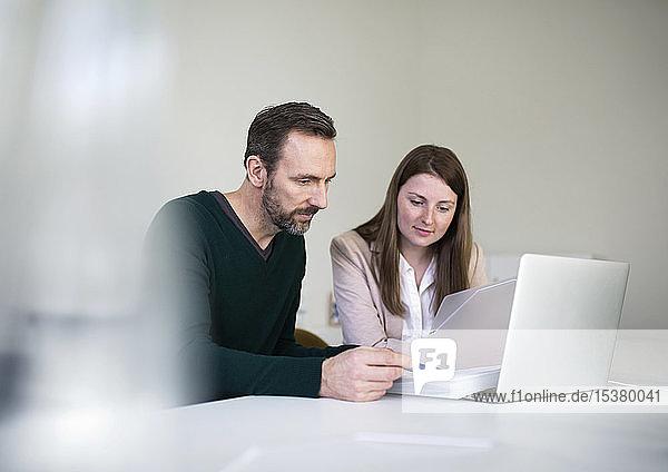Geschäftsmann und Angestellter mit Laptop und Dokumenten  die am Schreibtisch im Büro arbeiten