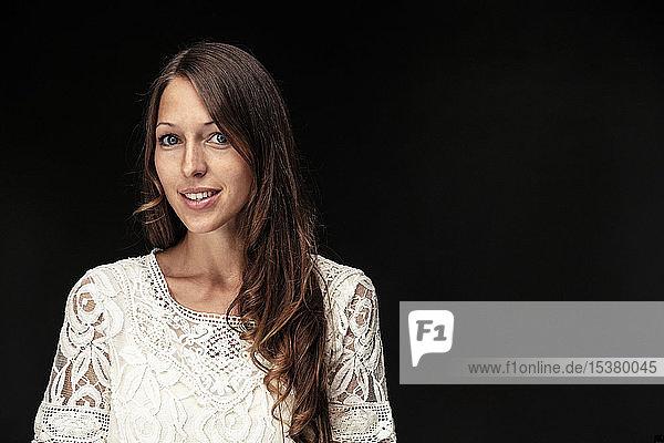 Bildnis einer jungen Frau mit langen braunen Haaren vor schwarzem Hintergrund