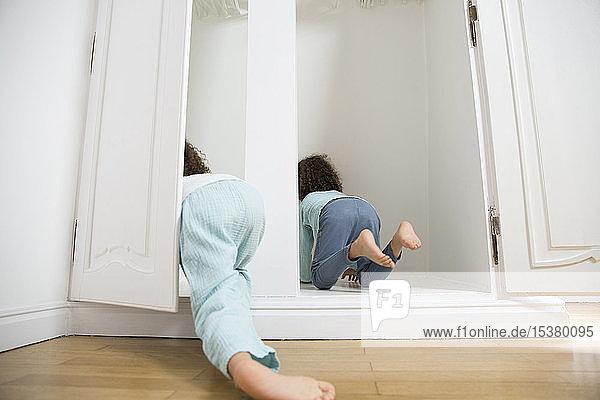Zwei Zwillingsbrüder kriechen zu Hause in die Garderobe