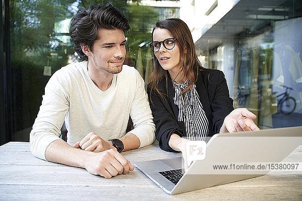 Geschäftsmann und Geschäftsfrau mit Laptop-Meeting in der Stadt