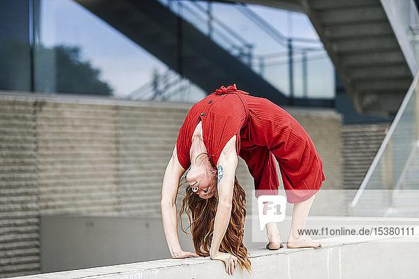 Sportliche junge Frau macht Akrobatik an einer Betonwand