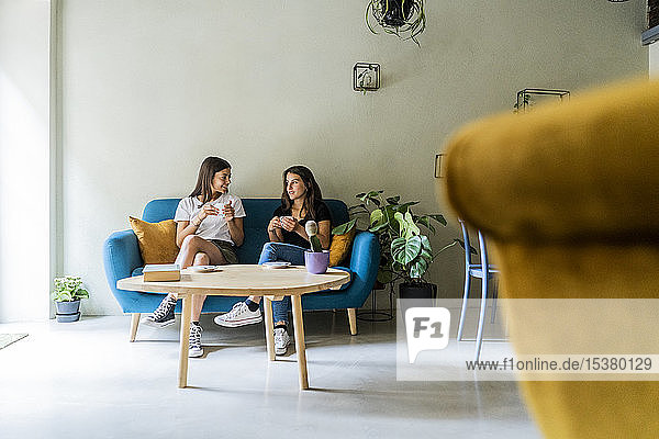 Two young female friends sitting on a couch in a cafe talking