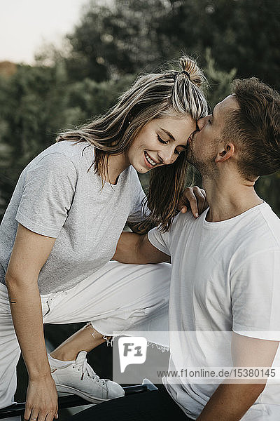 Portrait of young smiling couple  man kissing her on the forehead