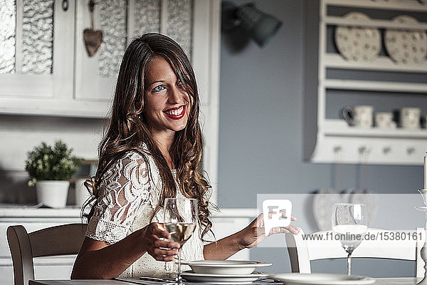 Portrait of smiling young woman sitting at laid table in country style kitchen