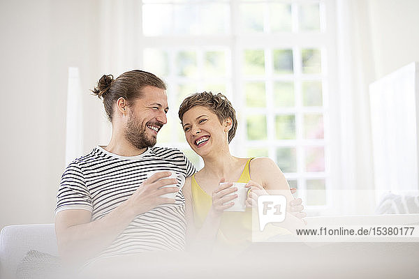 Happy young couple holding cups on couch at home