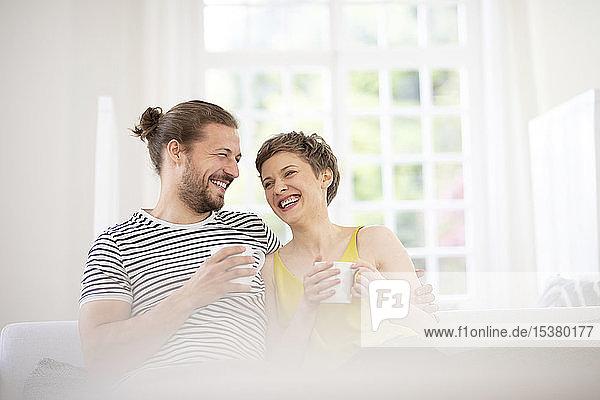Glückliches junges Paar hält zu Hause Tassen auf der Couch