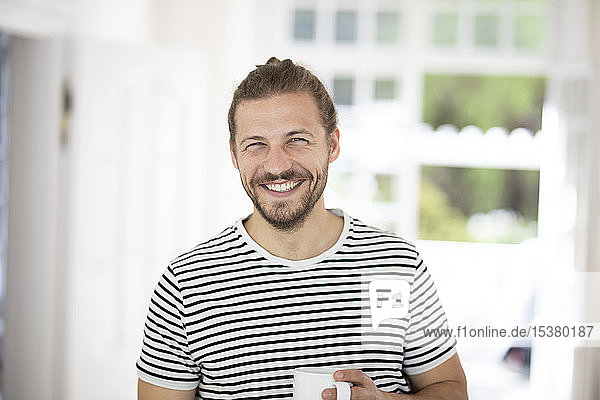 Portrait of smiling young man holding cup of coffee at home