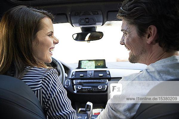 Glückliches Paar im Auto mit Frau am Steuer