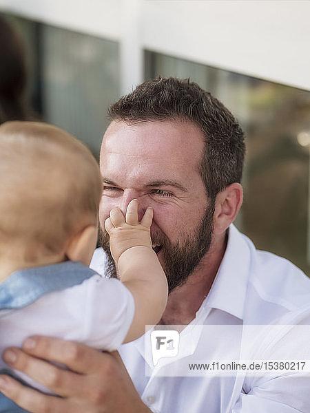 Mann spielt mit Mädchen und kneift sich in die Nase