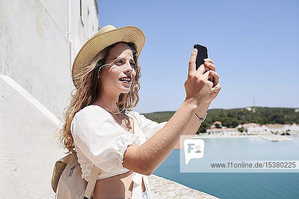 Junge Frau beim Selfie an der Küste  Menorca  Spanien