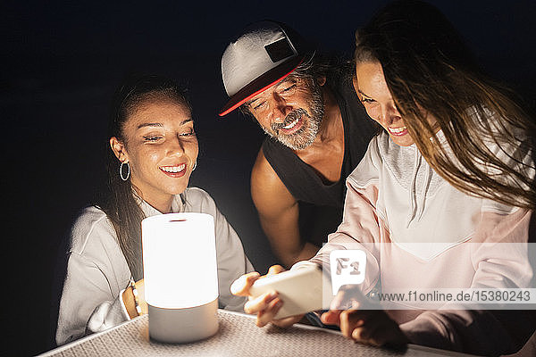 Zwei junge Frauen und ein reifer Mann mit Smartphone und LED-Licht auf nächtlichem Campingtisch