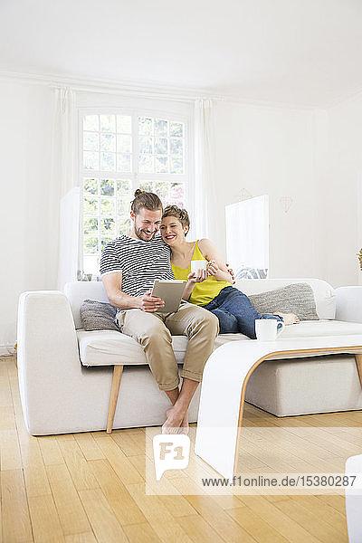 Glückliches junges Paar mit Tablette auf der Couch zu Hause