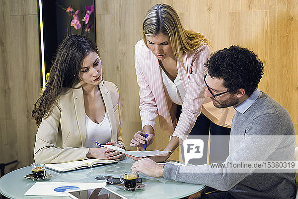 Three business people having a meeting in modern office discussing document