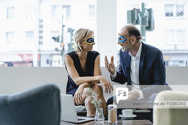 Geschäftsmann und -frau mit Superhelden-Masken  die eine Besprechung abhalten