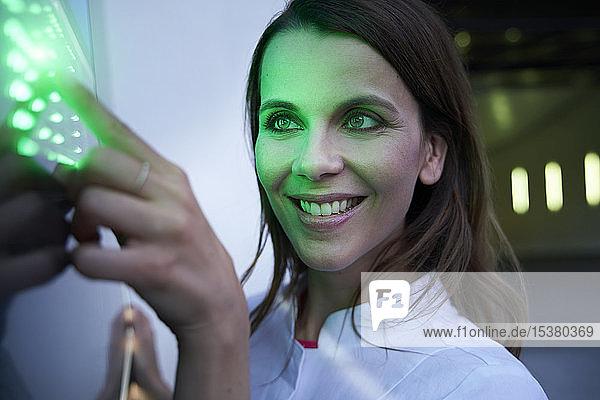Nahaufnahme einer lächelnden Frau  die einen Touchscreen mit grüner LED berührt