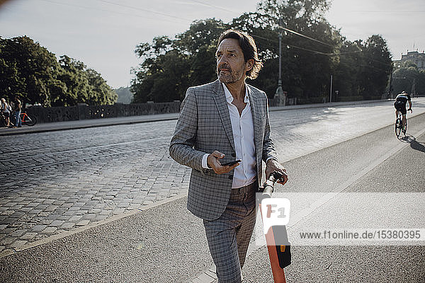 Businessman renting an e-scooter in the city