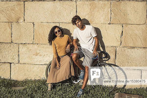 Junges Paar mit Fahrrad  an Steinmauer gelehnt  sieht cool aus Junges Paar mit Fahrrad, an Steinmauer gelehnt, sieht cool aus