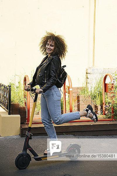 Porträt eines lächelnden Teenager-Mädchens auf einem Roller stehend